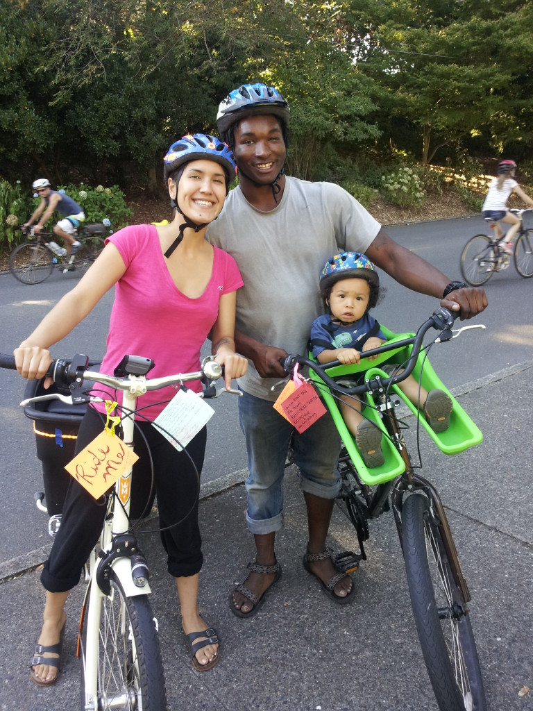 A family poses with their child in a bike seat.